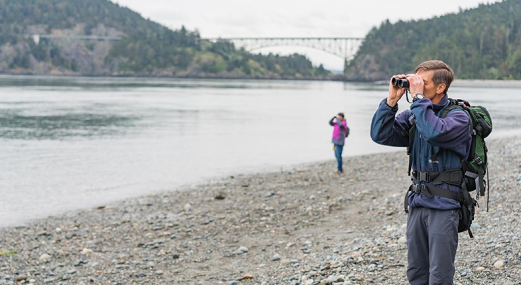 Man using binoculars on the beach. In the background the Deception Pass bridge spans Fidaglo island from the mainlain.