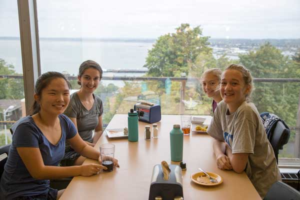 Four female high schools students sitting around a table in a dining hall, smiling at the camera.