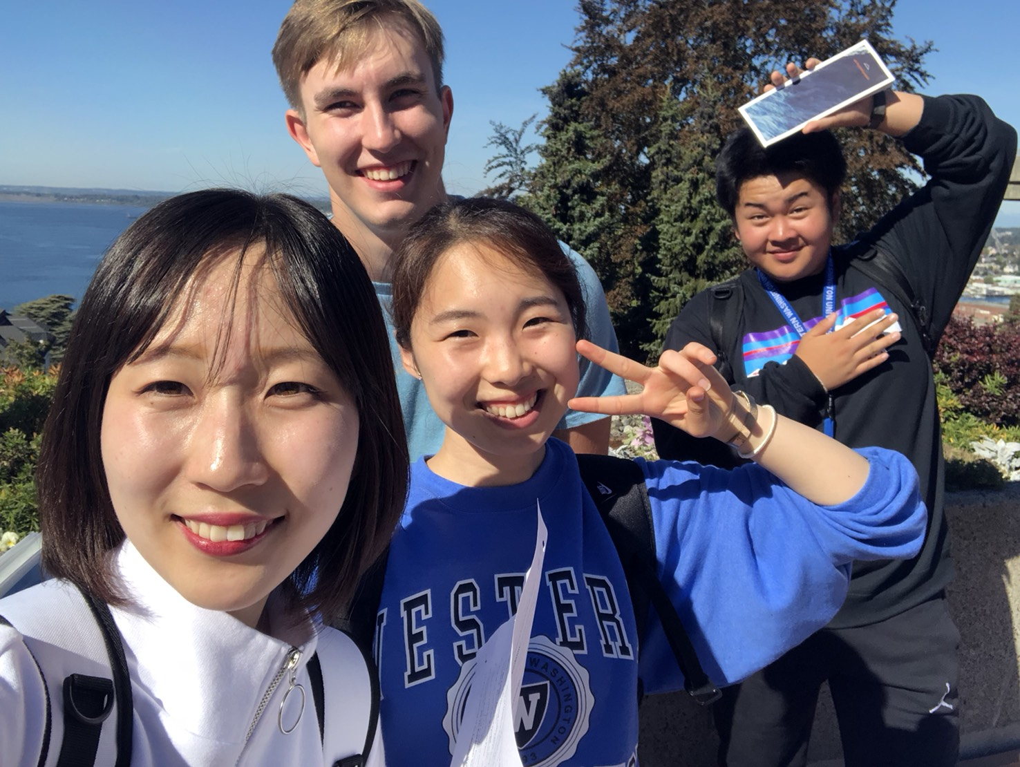 a group of international students are all smiles as they mug for the camera on a blue sky day.