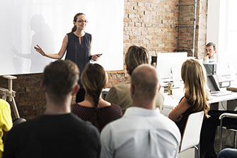 A woman speaks at the front of a group of students, gesturing at a white board.