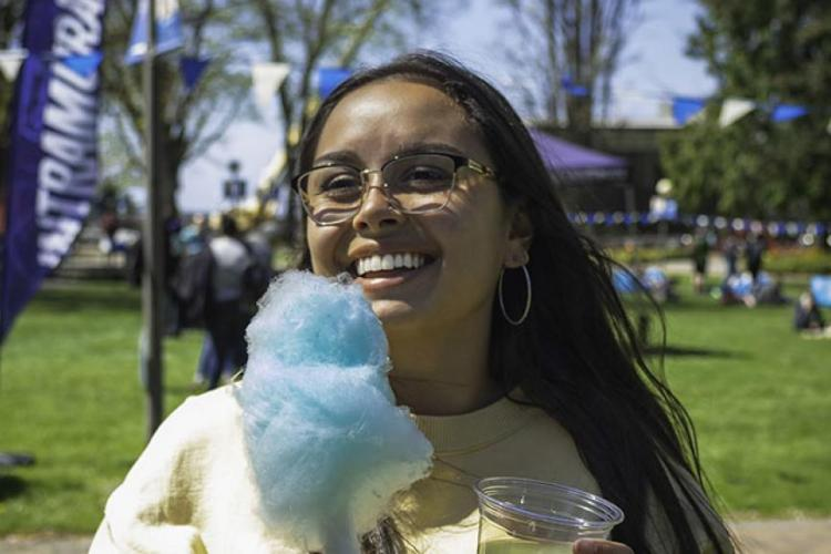 Smiling student stands in a landscaped green area, holding a cotton candy in her hand. The sky is blue and she's in a tshirt.