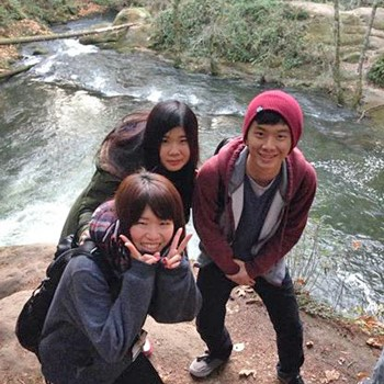 Three international students pose for the camera outside in nature, alongside a river