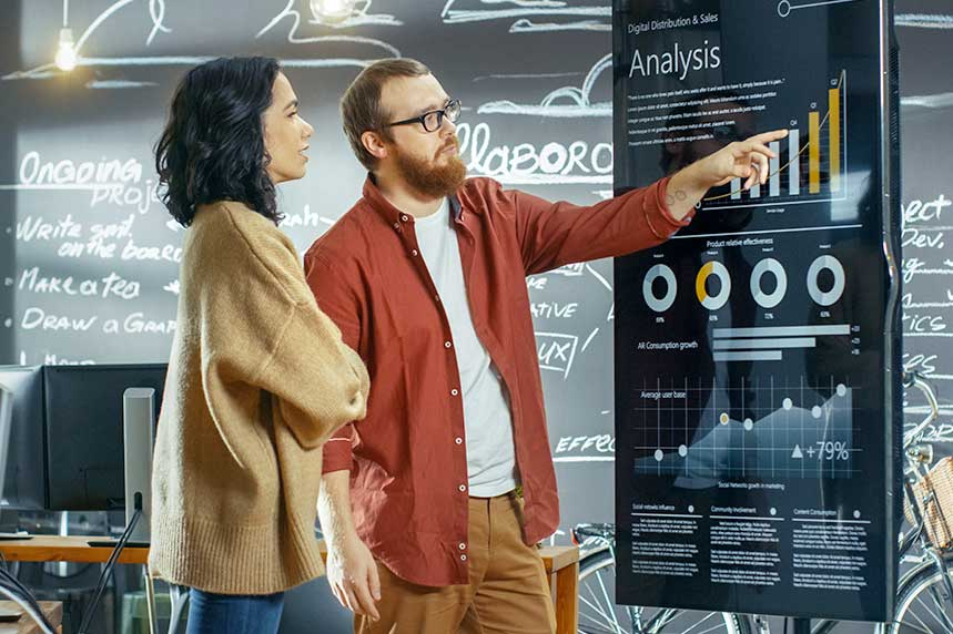Two Digital Marketing Strategists work on strategy in front of a whiteboard