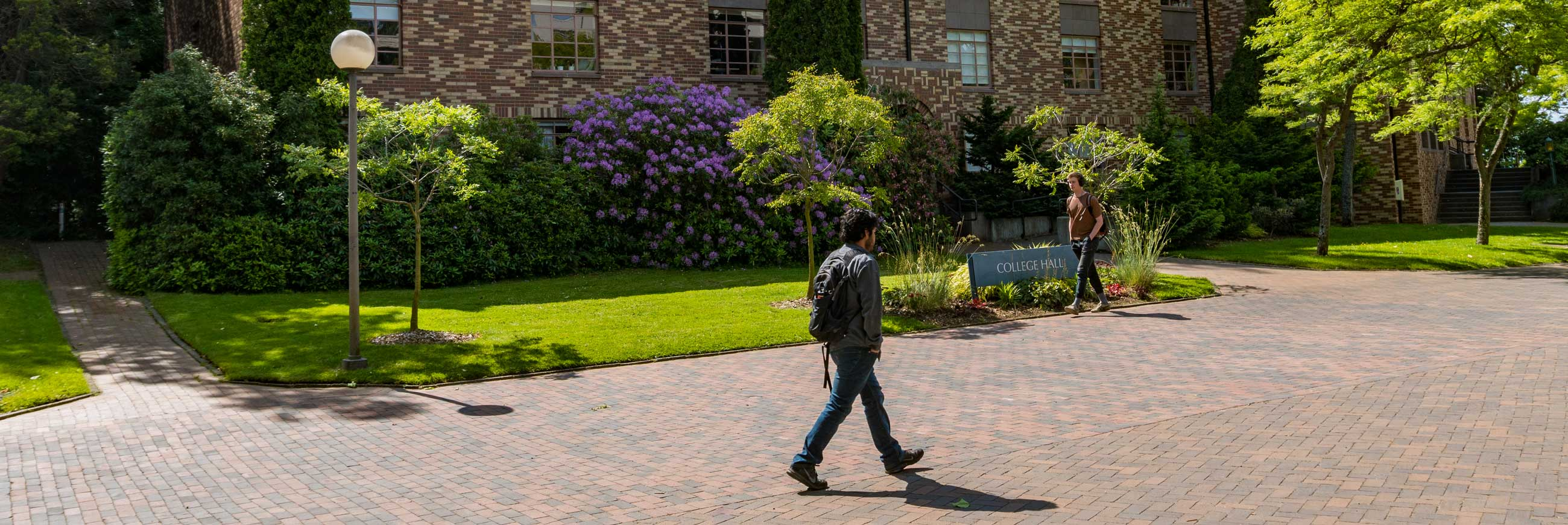 Two students walk in front of College Hall, the home of Outreach and Continuing Education at Western