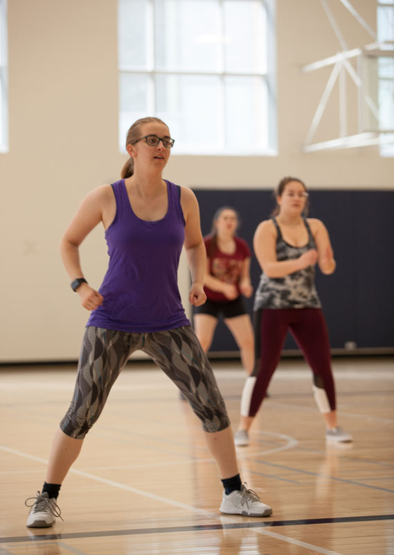 A woman in fitness gear works out in a gym with several other people.