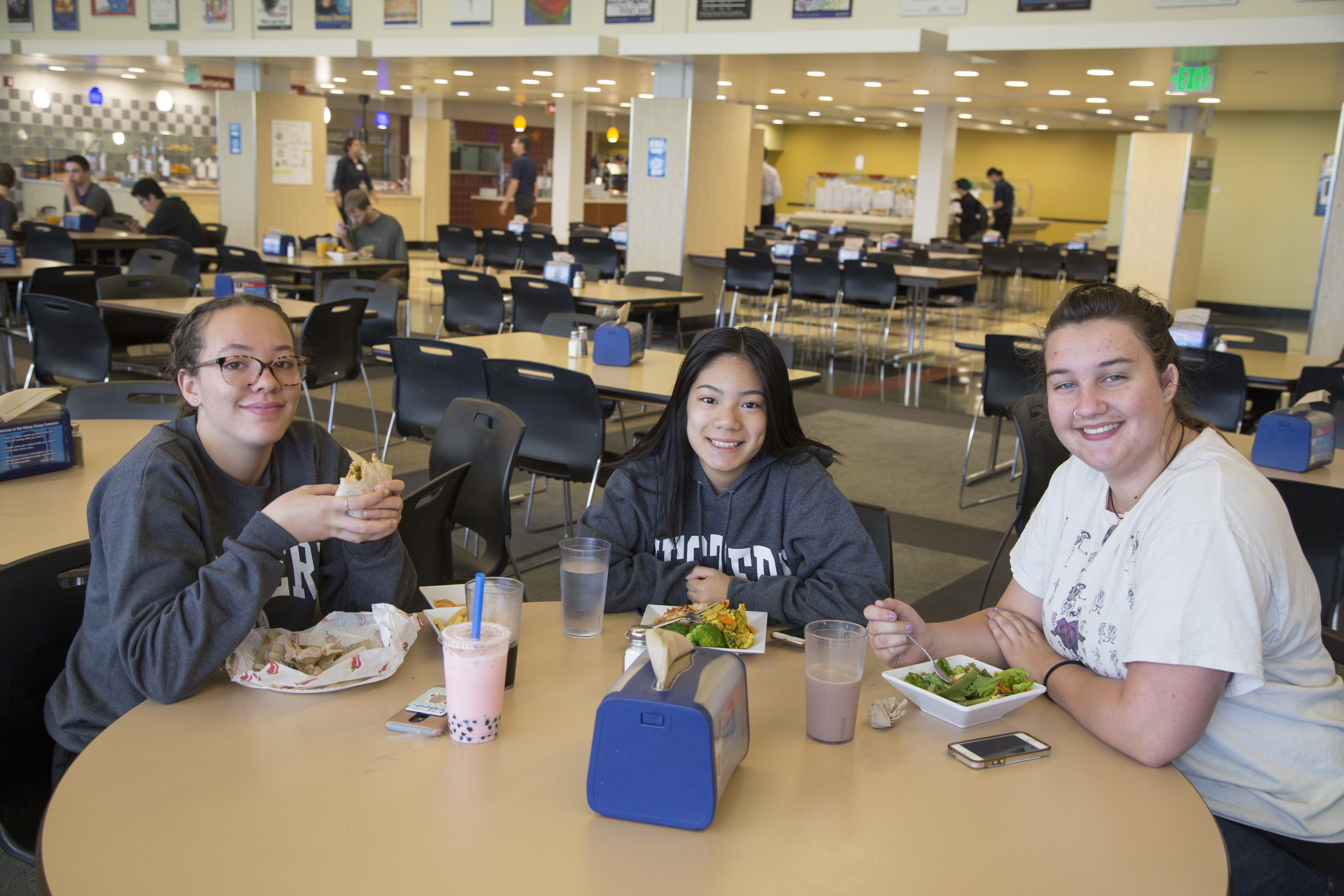 Three College quest students sit around a cafeteria table