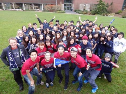 Group of WWU-AUAP students in matching red and blue t-shirts stand outside on the campus lawn in a celebratory pose.
