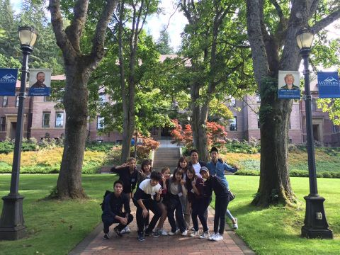 Group of WWU-AUAP students stand in front of Old Main building surrounded by green lawns and tall trees in the summer