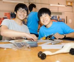 Two male youth students working on model race cars in a classroom